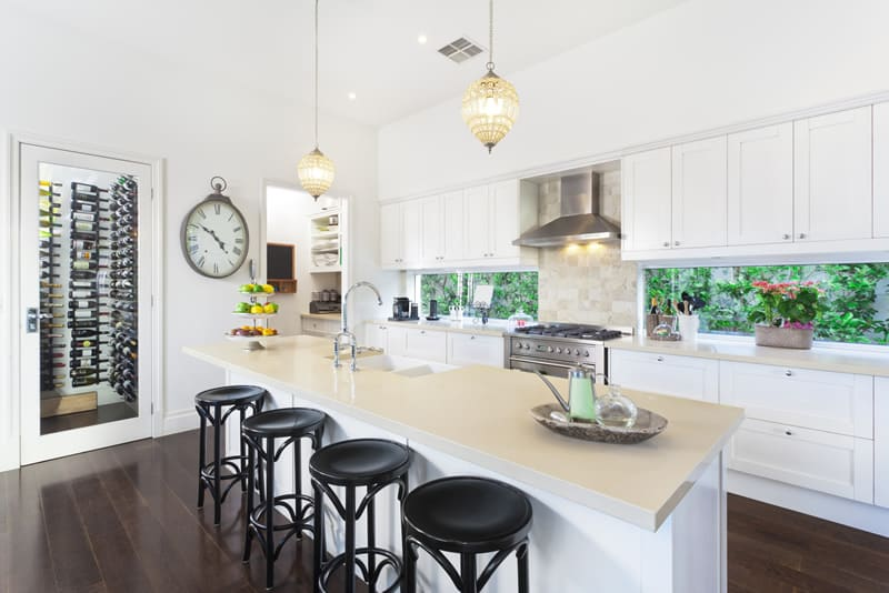 Contemporary kitchen with white cabinets, quartz countertops and wine storage pantry