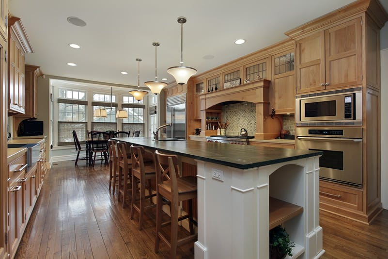 Custom kitchen with white cabinet island with dark countertops and breakfast bar