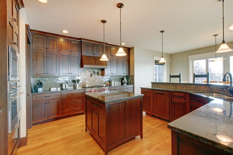 Custom solid wood kitchen cabinets, gray backsplash tile and center island