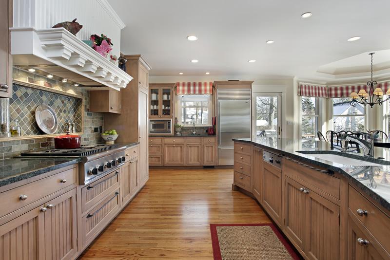 Large craftsman style custom kitchen with light wood cabinets. gas stove, slate backsplash and dark countertops
