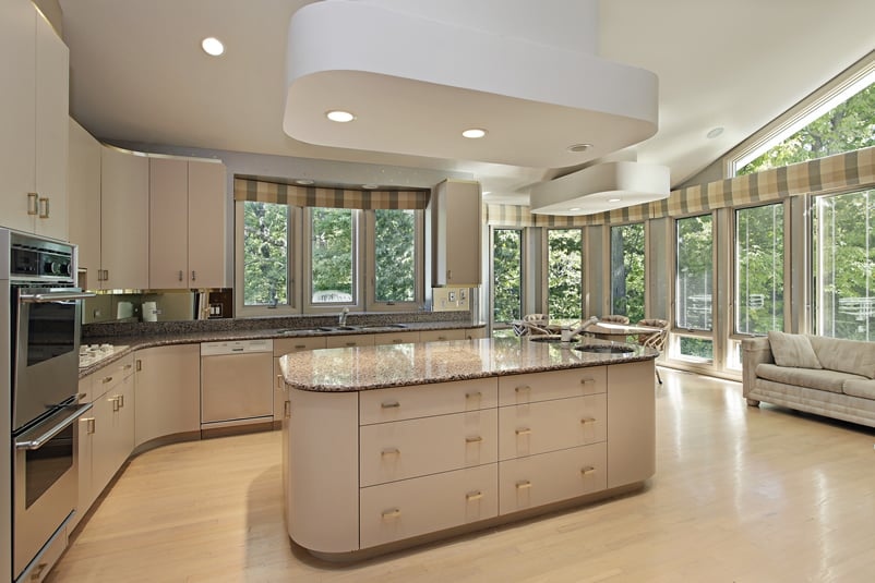 Modern kitchen with large rounded corner island and cream cabinets