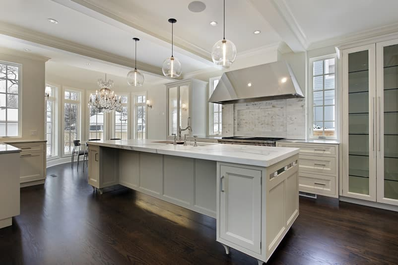 Modern white cabinet kitchen with beautiful light fixtures, pendant lights and dark wood floors