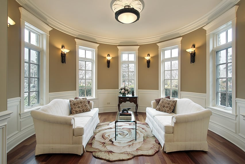 Round living room with wall sconces and multiple windows