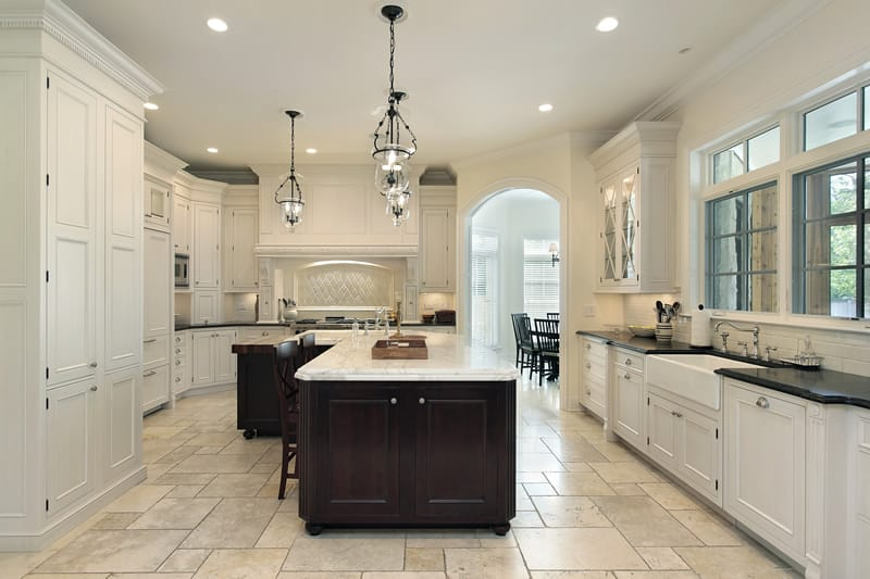 Upscale kitchen with marble counter island and white cabinets paired with dark countertops