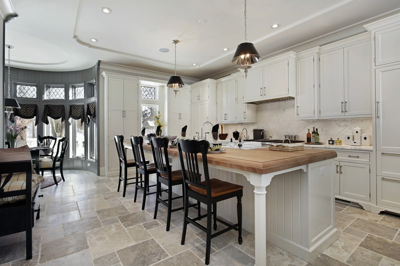 White cabinet kitchen with butcher block island in luxury home