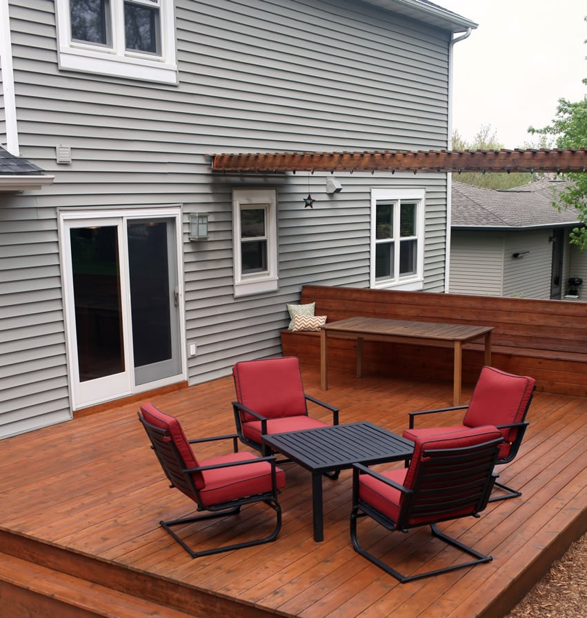 Backyard deck with pergola and red chairs and black table
