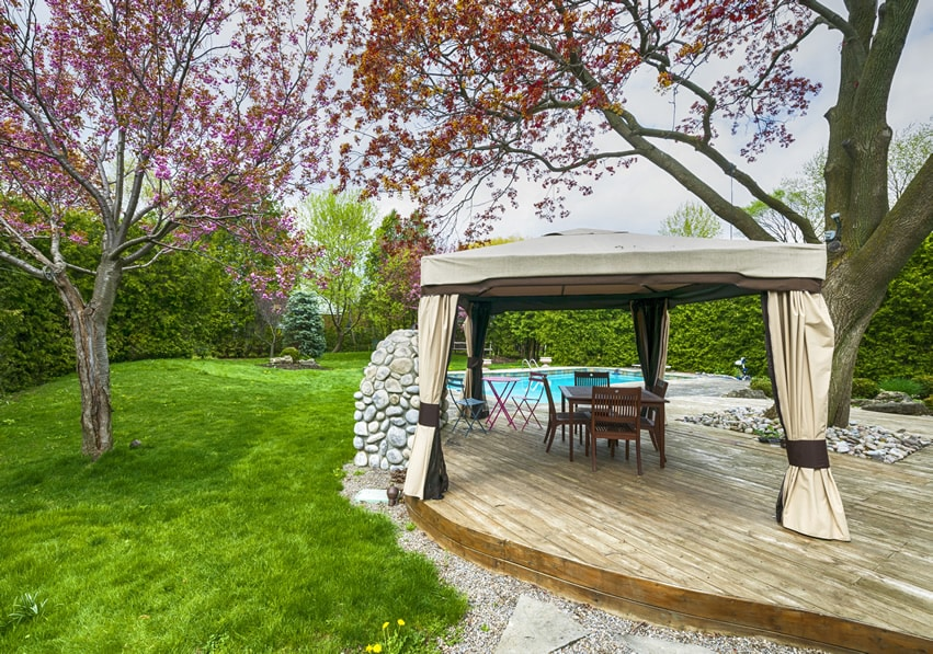 Backyard deck with pool by the lawn with canopy and-trees