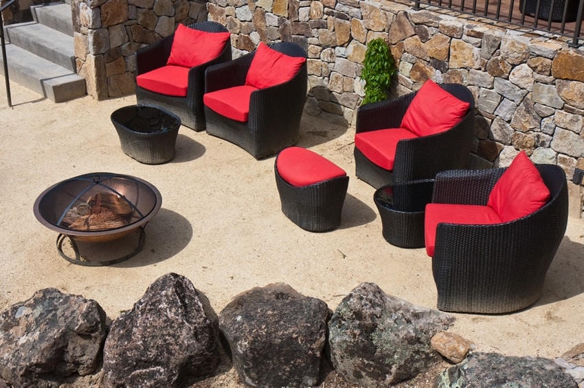 Backyard metal fire pit with comy red black chairs