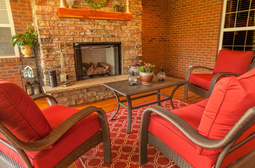 Indoor living room patio with brick fireplace and comfy furniture