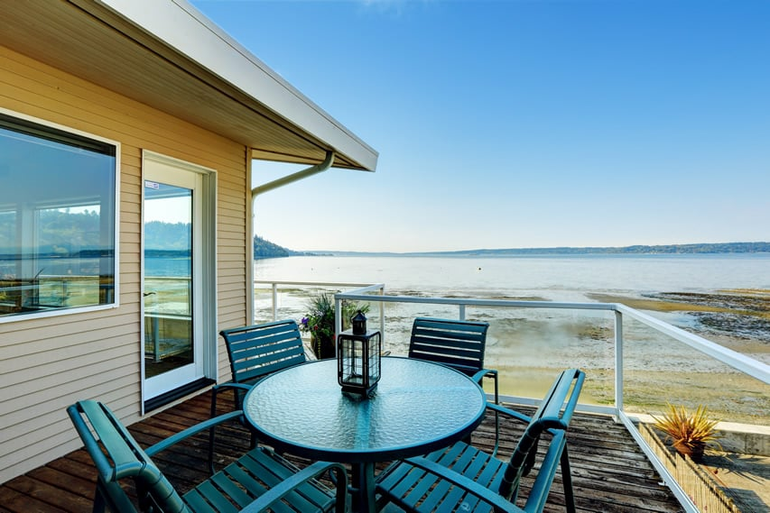 Oceanfront patio with outdoor dining table and chairs