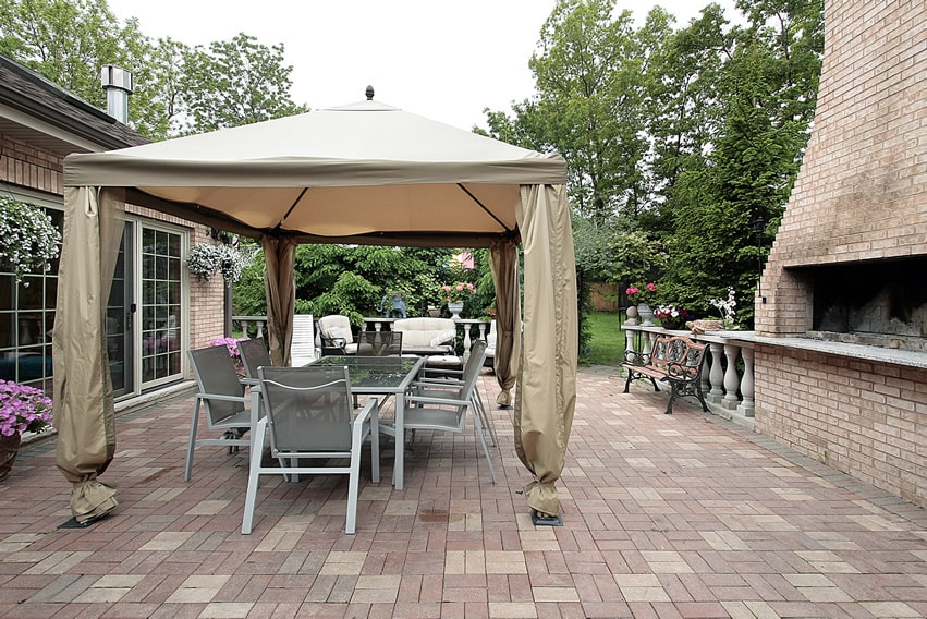 Open patio uses brick pavers in basket-weave patter with large outdoor brick barbeque