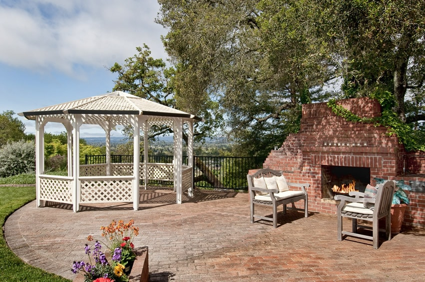 Semi-circular outdoor patio area with terracotta pavers, fireplace and white gazebo