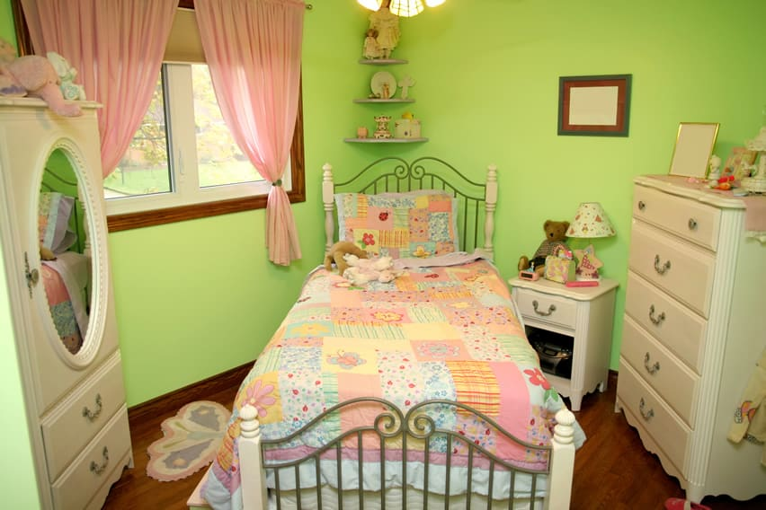Green tone girl's room with candy pink drapes and pastel colored patchwork bedding