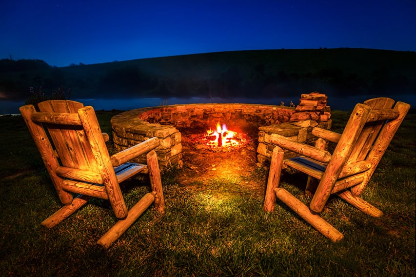 C-shaped rock fire pit with rustic wood chairs