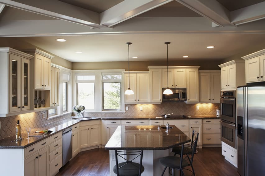 Traditional white cabinet kitchen with gray countertops and breakfast bar island