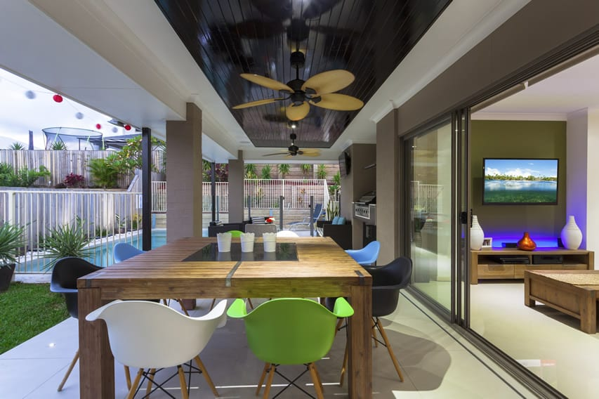 Modern covered patio with ceiling fan and large glass sliding door to living room
