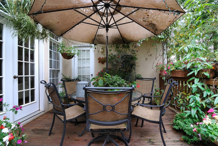 Garden patio area with weathered wood floor planks and umbrella