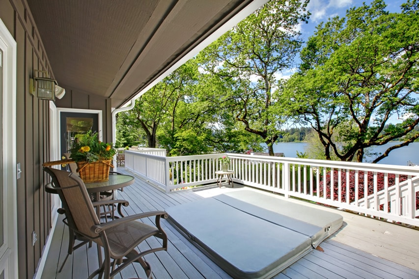 Deck with white railing and sunken hot tub