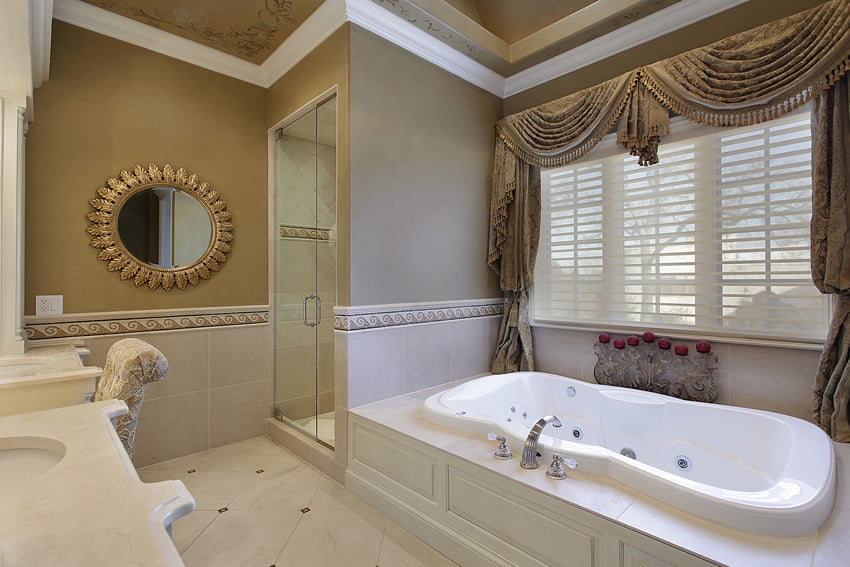 Bathroom uses cream colored ceramic tiles with ceramic tile borders in wave patterns and has an oversized jet tub