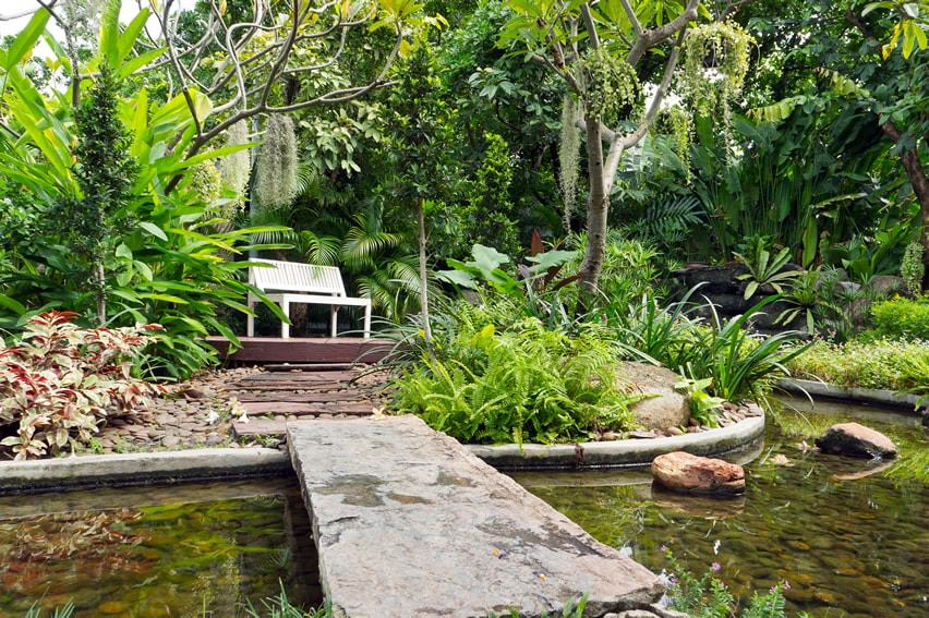 Garden sitting bench with bridge over pond