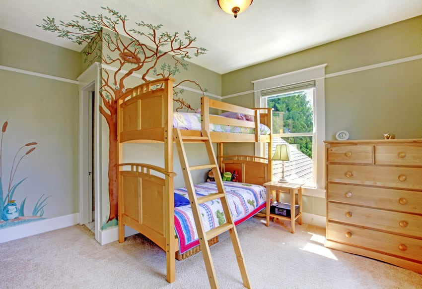 Green themed girl's bedroom with mural of a tree with birds nest