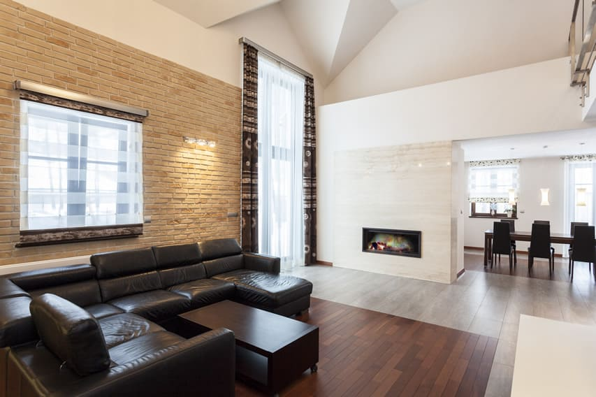 Grand design living room with exposed brick and marble fireplace