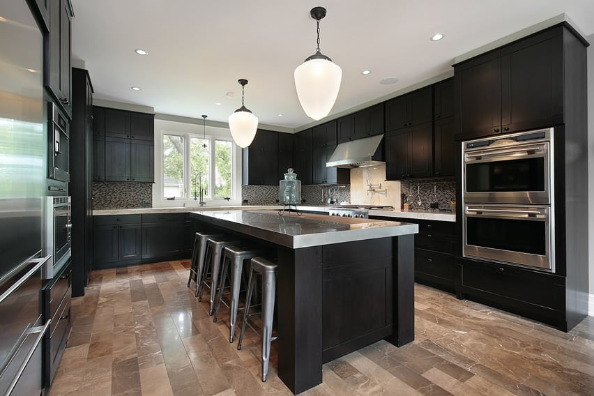 Modern kitchen with black wood cabinetry, stainless countertops and large island area with eat-in dining nook