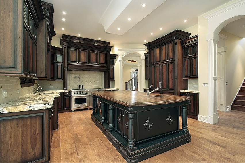 Kitchen with walnut cabinets, light granite counters, white arches and