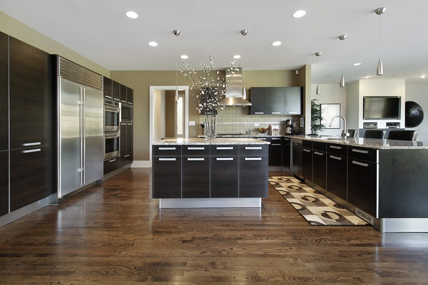 Large luxury kitchen with modern design, dark cabinets and stainless appliances