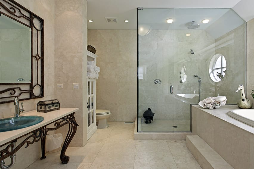 Luxury bathroom with natural non-slip stone tiles in cream and large step in shower