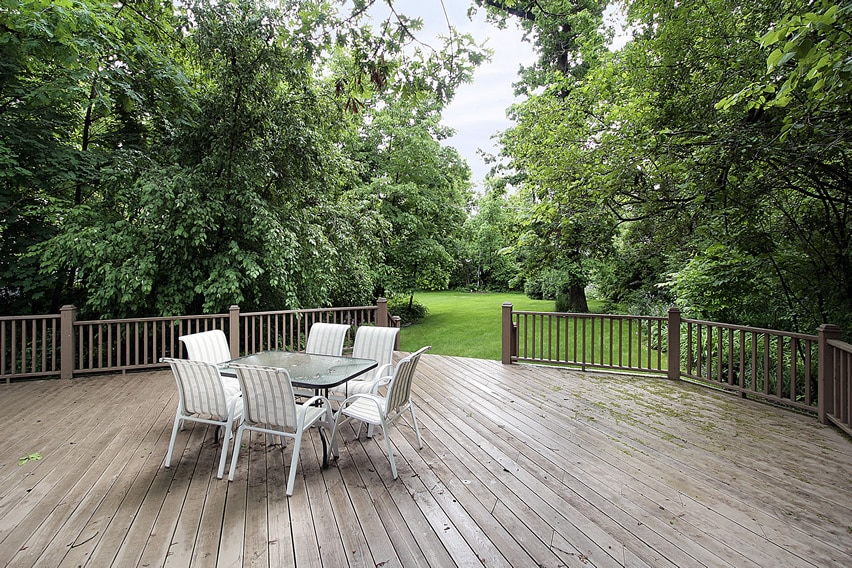 Large wood deck with railing and view of backyard trees