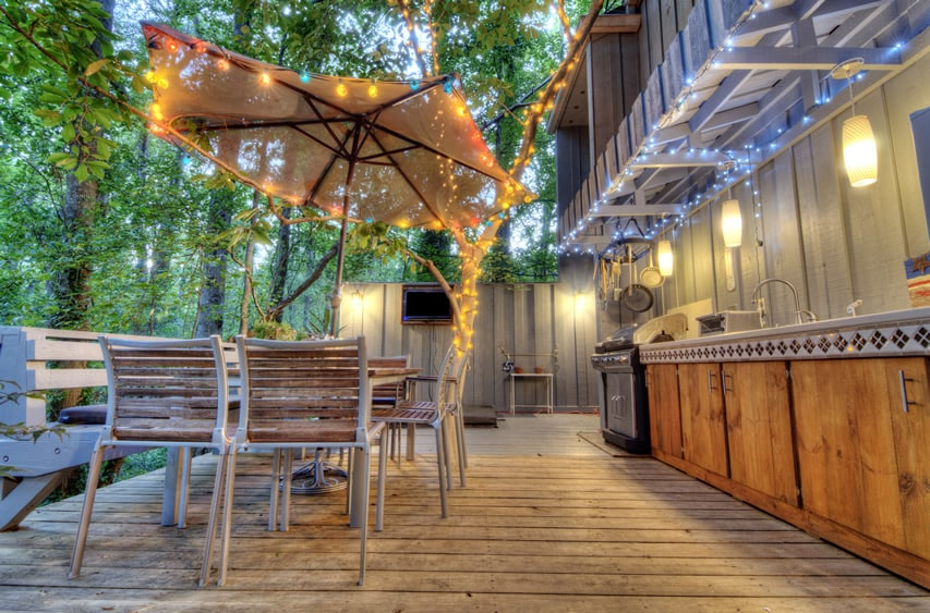 Lovely deck patio of a forest cabin with outdoor kitchen and lighting