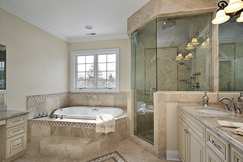 Bathroom combines light tan walls with natural stone tiles. Mosaic tiles used as borders and accents for the floor