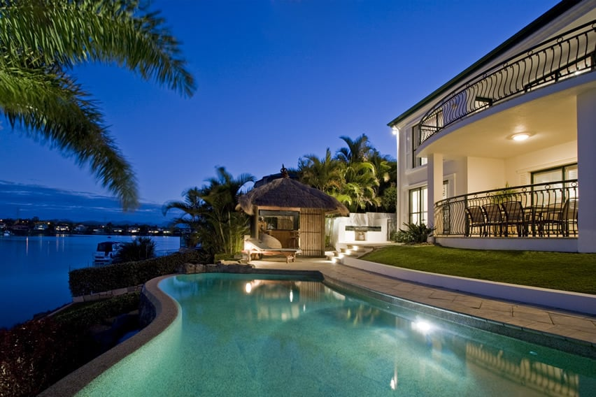 Luxury home pool with ocean view at night