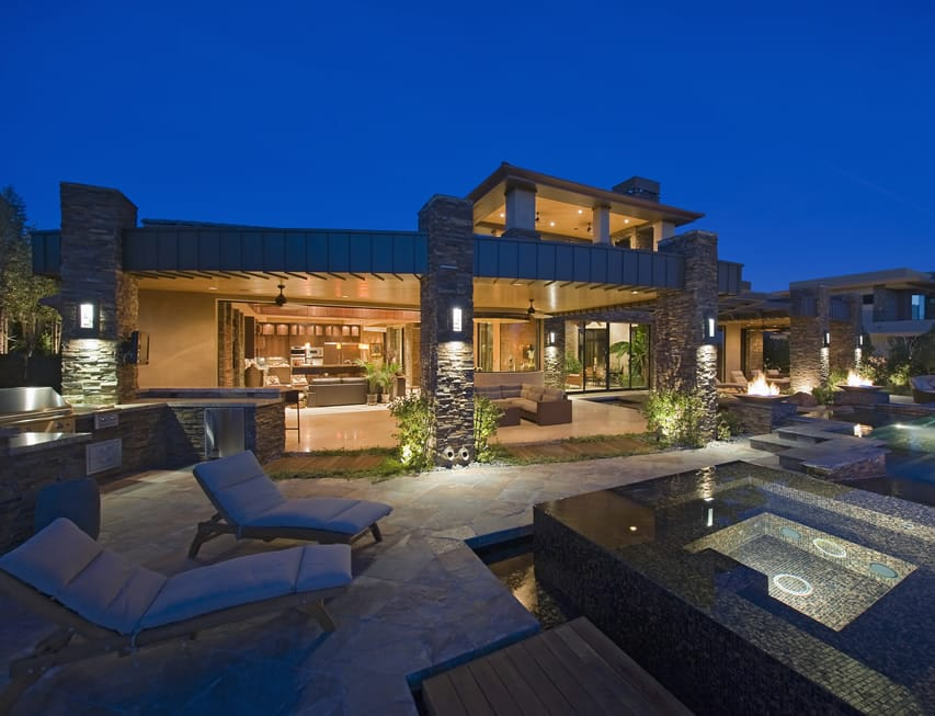 Outdoor lounging patio area overlooking pool, spa with outdoor kitchen