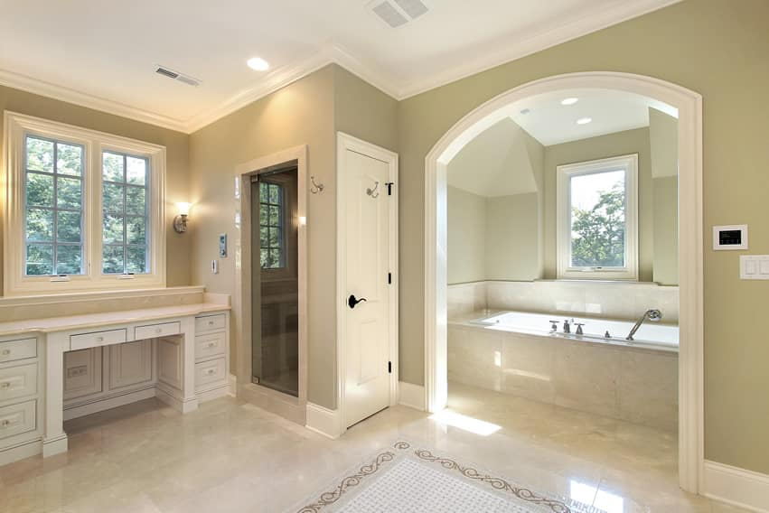 Large bathroom uses light-colored polished porcelain tiles with white arched room for tub