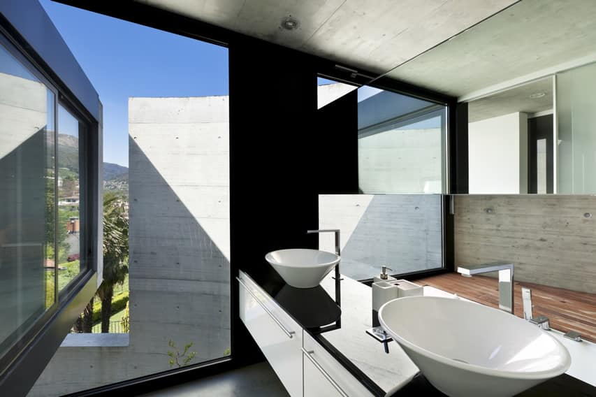 Modern bathroom with polished concrete and walls painted in black with vessel sinks