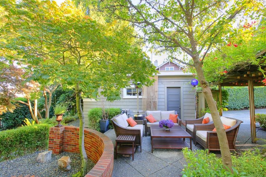 Garden patio with terrazzo flooring and pergola with climbing vine flowers