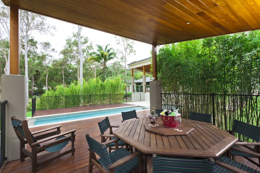 Tropical themed pool-side covered patio uses PVC decking with outdoor dining area