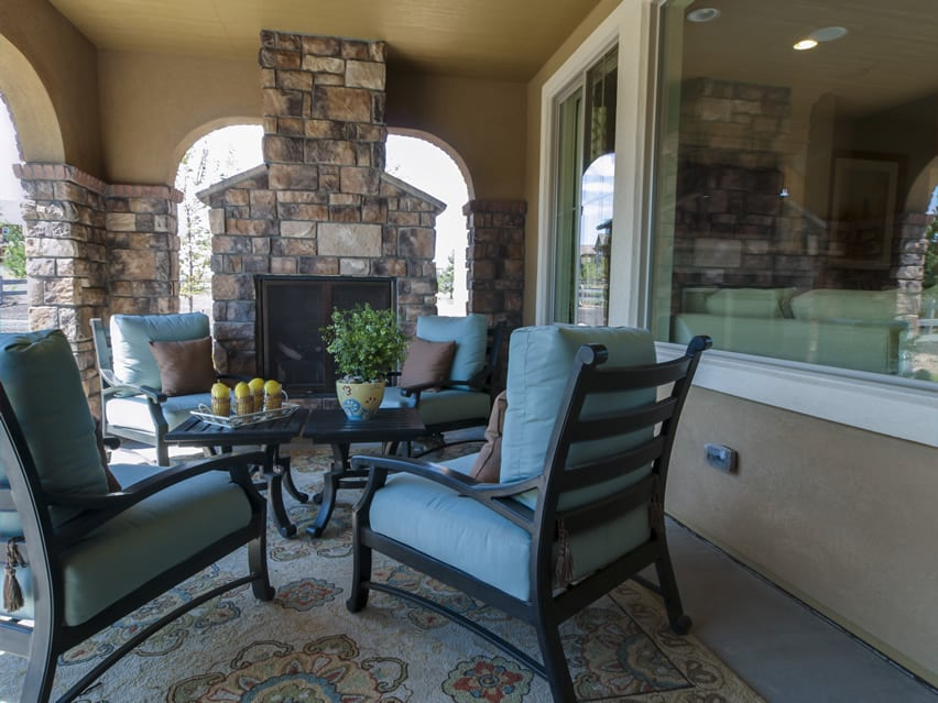 Cozy covered patio area with polished concrete floors and stone fireplace