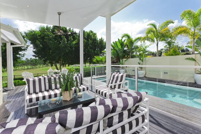 Modern pool patio design with weather wood planks and striped couches and chairs