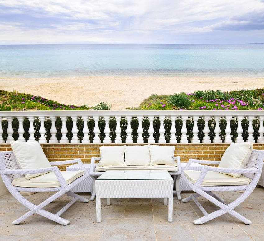 Home patio with beach view and white furniture