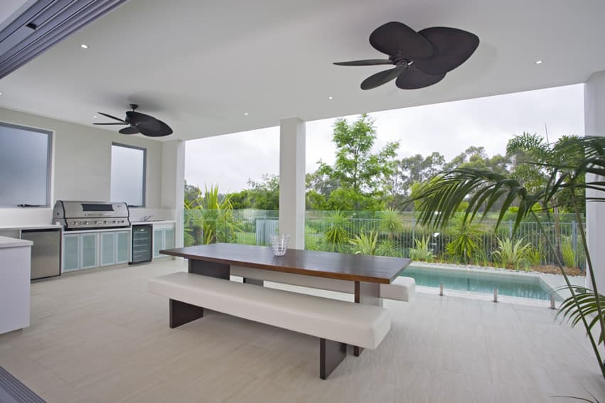 Minimalist and spacious pool patio with large barbeque and bench seating and dining table