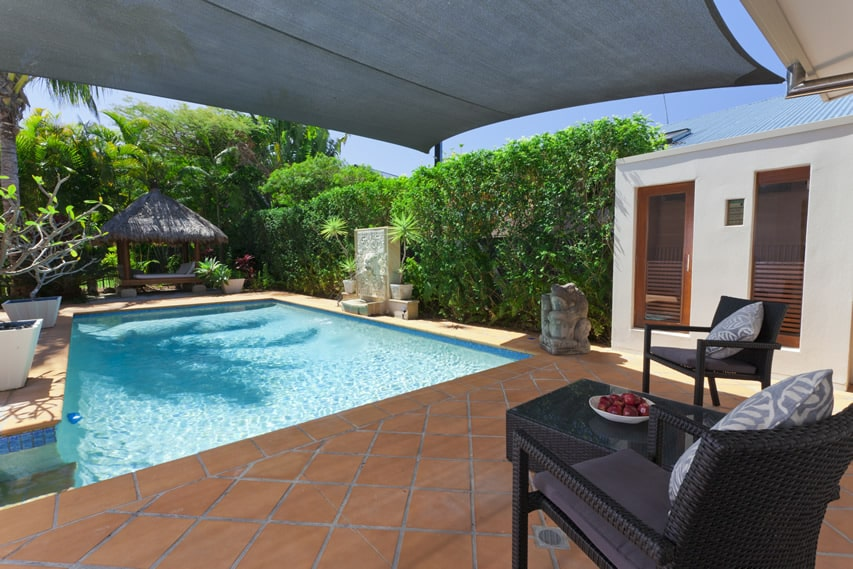 Pool lounge backyard with red ceramic tile floors, sunshade and cabana structure