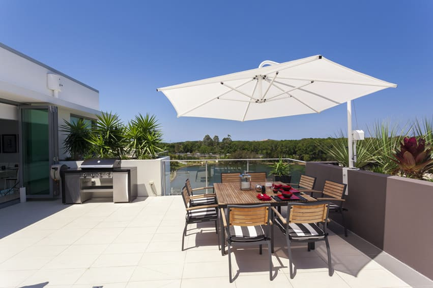 Sunny outdoor patio area with dining table and sunshade