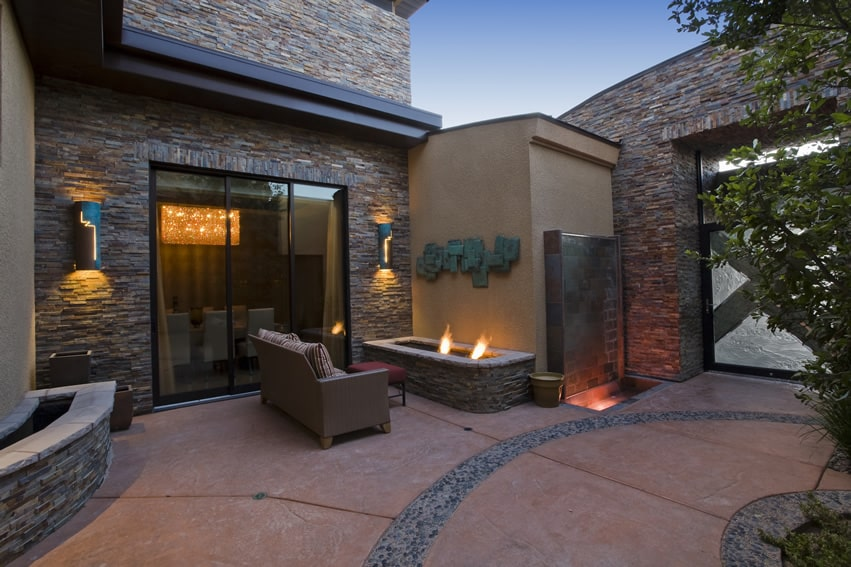 Luxury home open patio area with masonry tiled fireplace