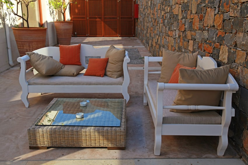 Courtyard patio with stone wall and cushioned outdoor furniture
