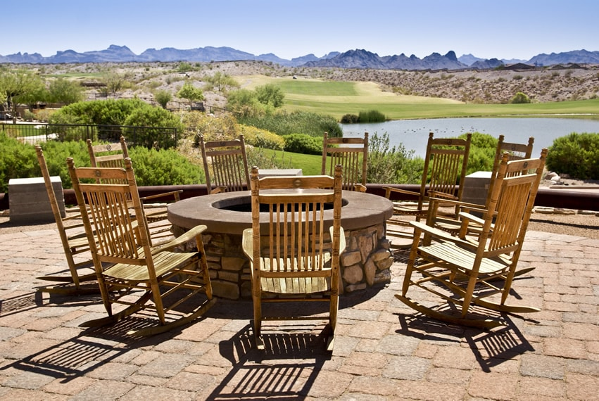 Rocking chairs around outdoor fire pit with amazing view