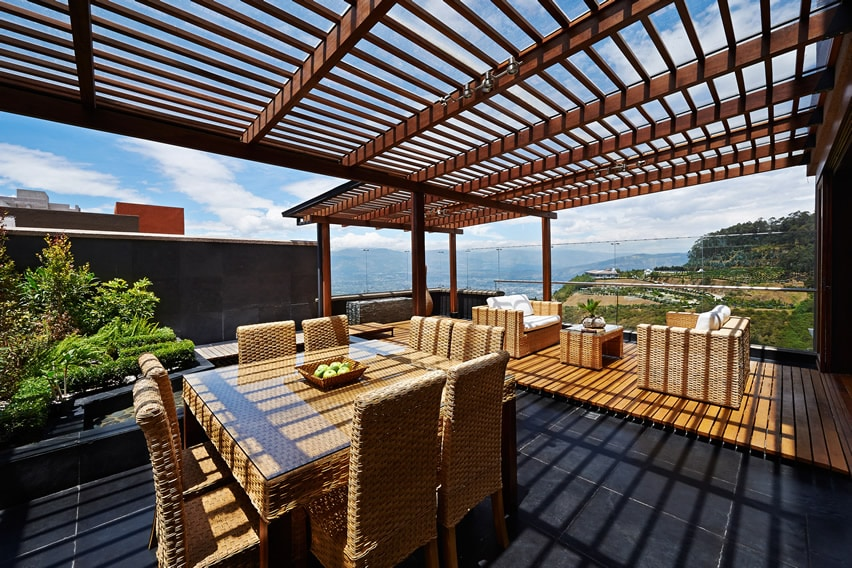 Rooftop deck pergola with wicker furniture