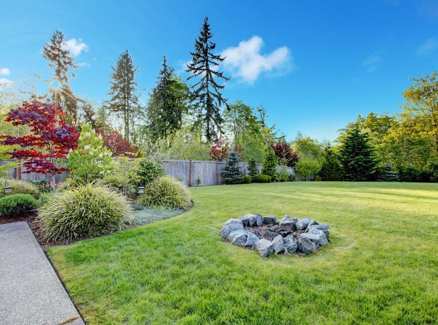 Simple backyard rock fire pit on lawn